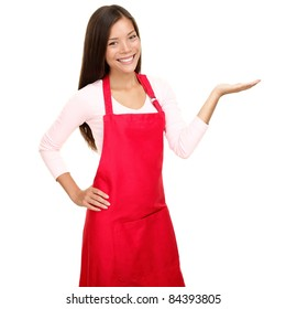 Small shop owner showing empty copy space in red apron. Woman smiling happy presenting with open hand palm. Friendly multiracial Asian Caucasian female model isolated on white background