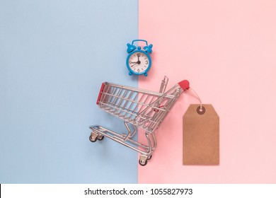 Small shopping cart with blank price tag and alarm clock on pastel background minimal creative concept