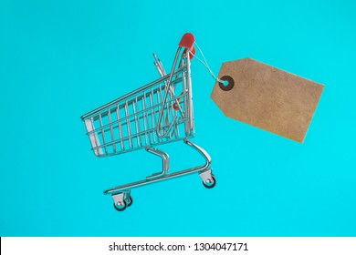 Small shopping cart with blank price tag on light blue background minimal creative concept