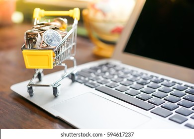 Small shopping cart contains coins on laptop and working space on wooden table in Coffee shop using as shopping online or marketing technology background concepts