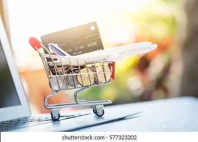 Small shopping cart contains credit or debit card and airplane on laptop for shopping online  or buying airplane ticket with nature background, business online concept.