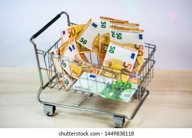 small shopping cart full of Euros, paper money, small bills