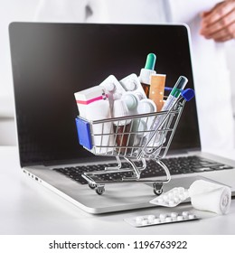 Small shopping cart full of medications in close-up and the computer in doctors office as medicine online purchasing concept