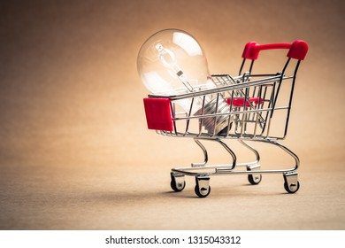 Small shopping cart with glowing light bulb for shopping idea, smart buying or energy saving concept