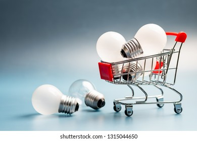 Small shopping cart with glowing light bulb for shopping idea, creative small business concept, smart buying or energy saving concept
