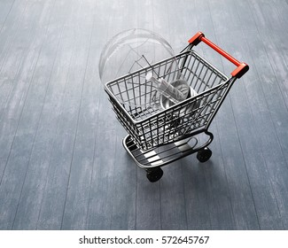 Small shopping cart with large light bulb, high angle view, on wooden floor background.