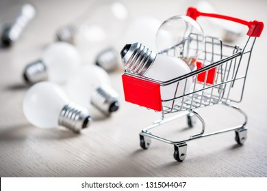 Small shopping cart with small light bulbs for shopping idea, creative small business (SMEs) concept, economy buying or energy saving concept