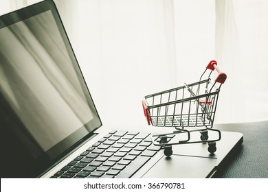 Small Shopping Cart On Laptop With Copyspace : Online Shopping Concept