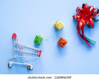 Small shopping cart , three gift boxes and red green gift bow,a shopping cart is dumping gift boxes have light shadows on blue pastel background have free or copy space,image for shopping gift concept