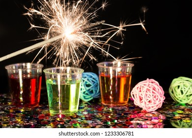 Small shot glasses and a burning sparkler in front of black background