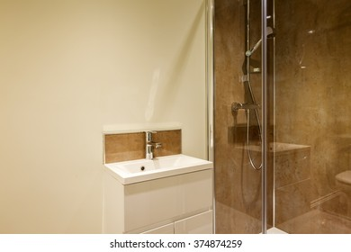 Small shower room containing double shower with glazed doors and small hand-basin