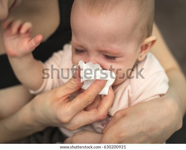 Маленький, больной, плачущий ребенок, которого мать протирает бумажным полотенцем
