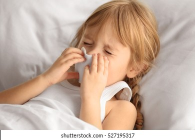 Small sick girl blowing her nose in bed