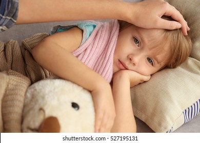 Small sick girl with Teddy bear in bed