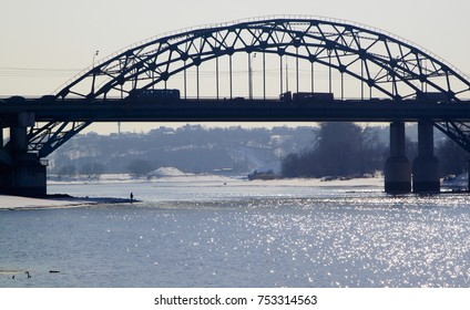 a small silhouette of a fisherman on the bank of a winter river under a railway bridge