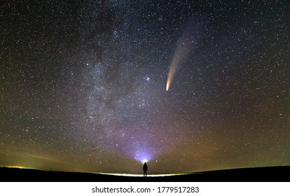 Small silhouette of a scientist with flashlight on his head pointing bright beam of light on starry sky with C/2020 F3 (NEOWISE) comet with light tail. Space exploration concept.