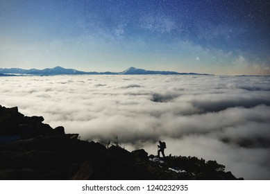 Small silhouette of tourist hiker with backpack and trekking poles climbing steep rocky mountain slope on background of blue starry sky, foggy valley filled with white clouds and snowy mountain tops.