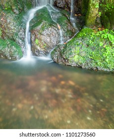 Small silky water fall running over moss covered rocks.