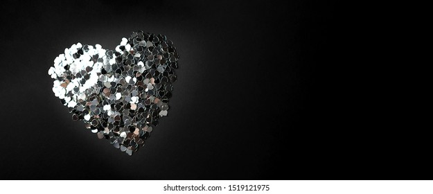 A lot of small silver confetti hearts laid out on a black background in a big heart. Place for text.