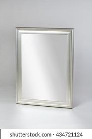 small silver framed modern mirror isolated on gray background