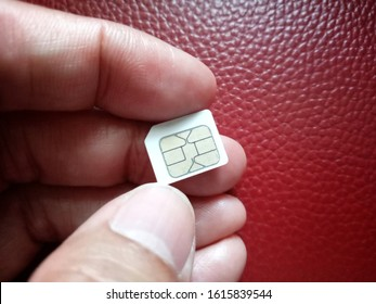 Small sim card in hand isolated dark red background.