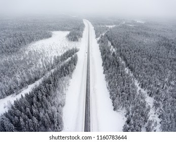 Small single car stands roadside on wintry road at blizzard, aerial view at straight northern route. Karelia, Russia