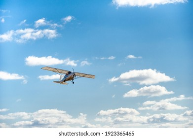 A small single-engine plane flying overhead against the blue sky.