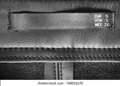 Small size clothes label on black leather as a background
