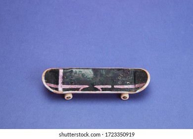 Small skateboard on blue background. tiny skate for fingers. fingerboard close up. copy space