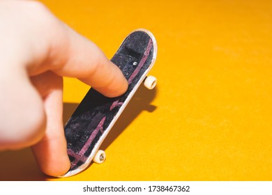 Small skateboard on yellow background. fingers on tiny skate. playing with fingerboard. home leisure concept. copy space