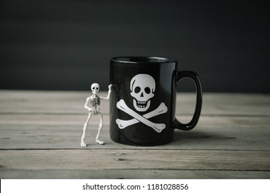 Small skeleton stands beside a black coffee mug that has a skull and crossbones on it on a rustic wooden surface with a black background.