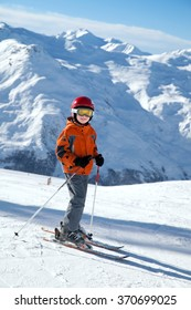 A small skier on piste in winter mountains