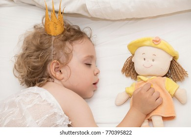 Small sleeping girl of two years in her white bed. Closeup