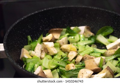 Small sliced king oyster mushrooms and Pak Choi are fried in a pan for healthy roasted vegetables