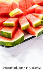 Small slices of red seedless watermelon on the tray for the party.