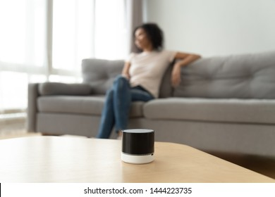 Small smart portable wireless speaker on table in living room with african american woman sit on sofa on background, mini stereo equipment for sound and digital assistance at home concept