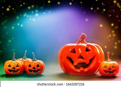 kleine Lächeln Orangen und ein großer LächelKürbis auf hellem, schwarzem, bunter Hintergrund ang Kopienraum und bunt mit funkelnden.