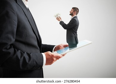 small smiley man got out of the tablet pc and offering money to the big man in formal wear over light grey background
