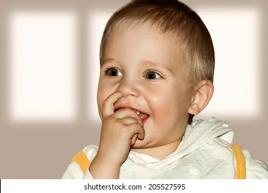 Small smiling baby with finger in the nose.