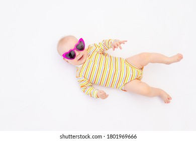 small smiling baby girl 6 months old lying on a white isolated background in bright sunglasses, space for text