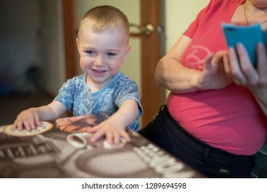 A small smiling child is studying drawing on the tablecloth, sitting on the woman's lap in the kitchen. A little smiling boy, 1,5 years old.