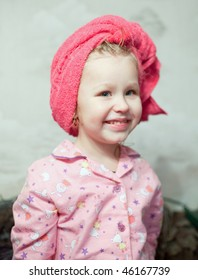 small smiling girl with a towel on a head