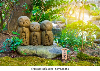 "Small smiling stone buddha monk statue (Nagomi Jizo). The Japanese characters mean ""The Jizo for good relationship"". Hasedera Temple, Kamakura, Japan"