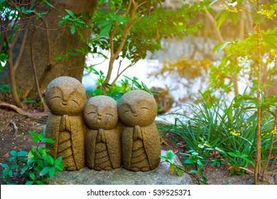 Small smiling stone buddha monk statue (Nagomi Jizo). Hasedera Temple, Kamakura, Japan