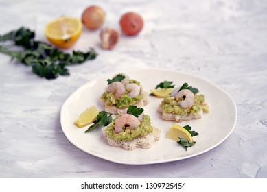 Small snack sandwiches on white bread with guacamole and shrimps on a white plate. Selective focus.