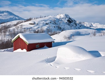 A small snow covered hunting lodge in the norwegian mountains with animal traces in the foreground and mountain summits in the background