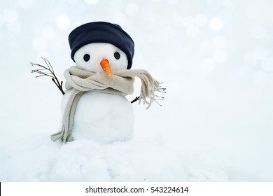 Small snowman in a cap and a scarf on snow in the winter. Festive background with a lovely snowman. Christmas Card, copy space