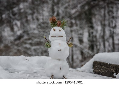 A small snowman on blurred snow background