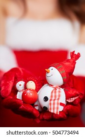 Small snowman with red scarf and hat at the hands of a model. Christmas shopping, preparations. Macro.