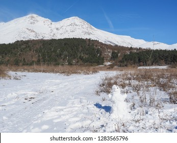 Small snowman, typical snow sculpture, built by children with sufficient snowfall. Beautiful winter landscape with snowy peaks of mount Velino in the Abruzzo Apennines, province of L'Aquila, Italy.